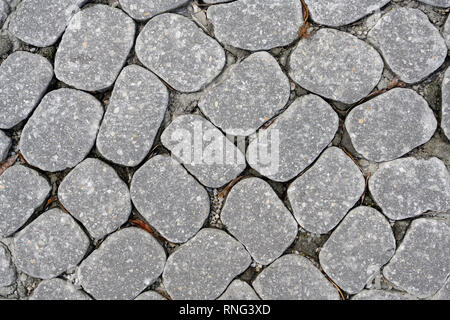 Gray granite cobblestone pavers used for a city street and useful as an abstract background or pattern. - Stock Image