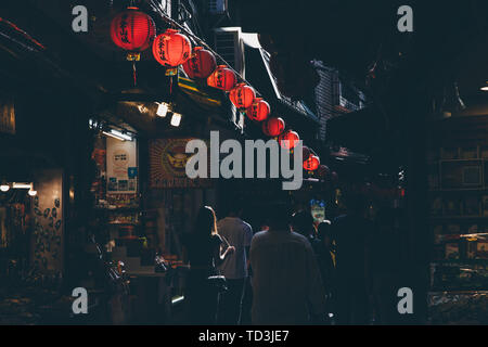 Jiufen, Taiwan - November 07, 2018: A young woman walks in the crowd at the Old Street market on November 7, 2018, in Jiufen, Taiwan - Stock Image