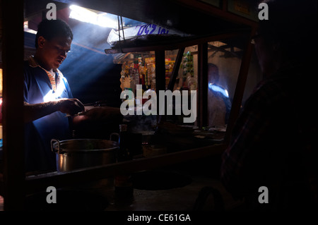 Balinese man cooking chicken satays in food stall at the Ubud Markets, Bali Indonesia - Stock Image