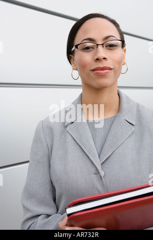 African businesswoman holding binder - Stock Image