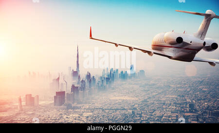 Private jet plane flying above Dubai city in beautiful sunset light. Modern and fastest mode of transportation, business life. - Stock Image