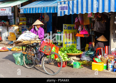 NHA TRANG, VIETNAM - DECEMBER 18: Vietnamese women in the traditional conical hat at the wet market on December 18, 2015 in Nha Trang, Vietnam. - Stock Image
