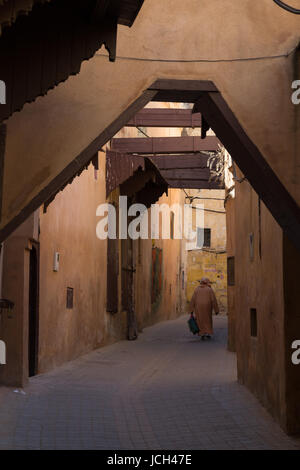 A man walks through a covered alleyway in Meknes, Morocco - Stock Image