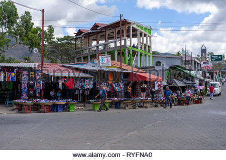 Unfinished building is surrounded by market stalls on a street in Jinotega, Nicaragua. - Stock Image