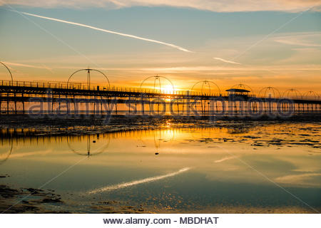 Southport Pier at sunset, showing the meal arches and stays of the bridge at sunset with a jet stream in the sky, which is reflected, England UK - Stock Image