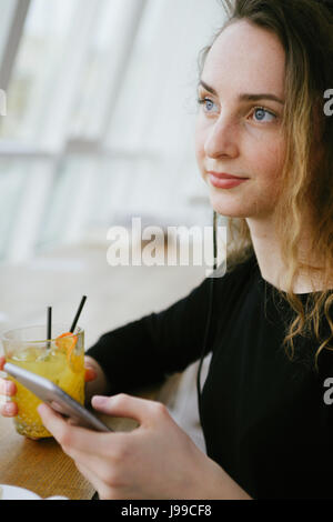 Young trendy woman holding an orange cocktail and listening to music - Stock Image