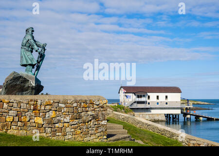 Statue of Coxswain Richard (Dic) Evans with new RNLI Lifeboat Station beyond. Moelfre Isle of Anglesey Wales UK - Stock Image