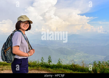 Teens girl hiker wear a cap and glasses with backpack is standing and smiling happily on high mountain at scenic - Stock Image