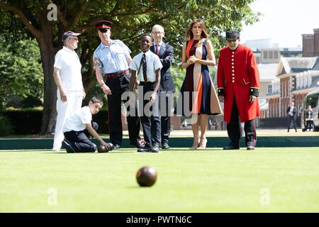 U.S First Lady Melania Trump and Philip May, husband of British Prime Minister Theresa May, try their hand at bowls during a visit to the Royal Hospital Chelsea July 13, 2018 in London, United Kingdom. - Stock Image