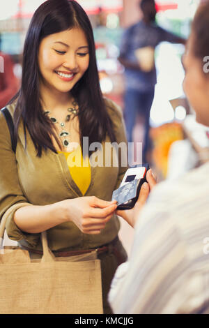 Female shopper with credit card using touchless payment in store - Stock Image
