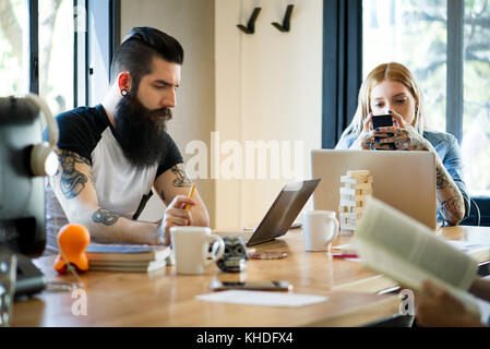 Working in shared casual office - Stock Image
