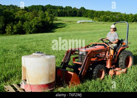 Hard working woman female farmer, fastest-growing group of farmers, moving water for pigs livestock with Kubota tractor, outside Decorah, Iowa, USA - Stock Image