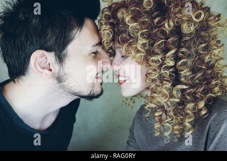 Portrait of a natural caucasian couple of young woman with curly blonde hair and man from side, they are happy and give affection each other - Stock Image
