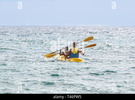 Adventurous traveling couple rowing a boat on a perfect scenic at sea - Stock Image
