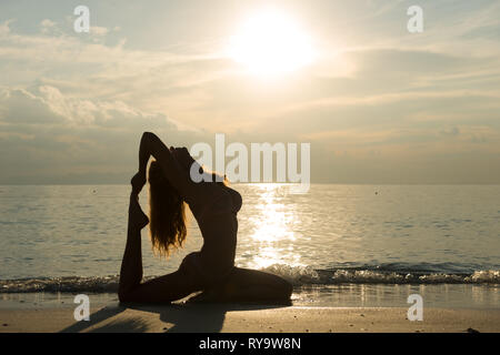 Silhouette of a girl in pigeon pose, practicing yoga on the beach, Thailand - Stock Image
