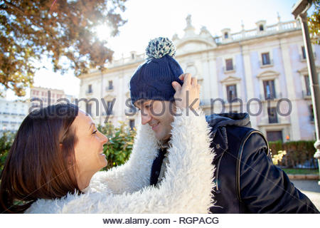 Young girl helps her boyfriend put on a blue wool hat in a public park. - Stock Image
