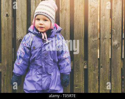 little girl wearing purple coverall standing by the wooden fence - Stock Image