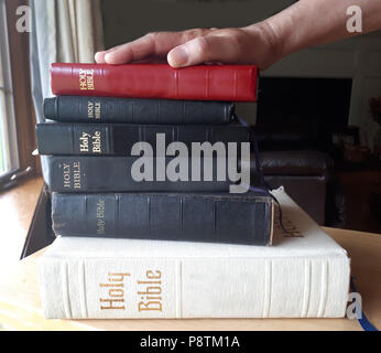 A hand on top of a stack of bibles is ready to swear the truth - Stock Image