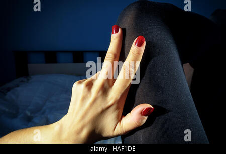 Womens hand on her leg in black tights stockings with red nails lying on a bed with crossed legs with a defocused - Stock Image