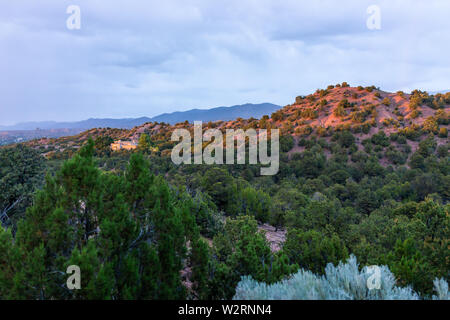 Sunset in Santa Fe, New Mexico mountains in Tesuque community neighborhood with houses, green plants and blue sky - Stock Image