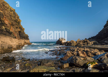 Waves roll in to Church Cove on the Lizard Peninsula, near Lizard village in Cornwall, England - Stock Image