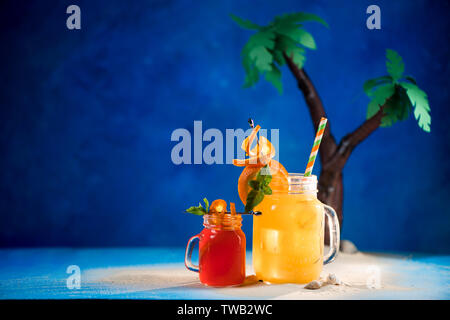 Decorated tropical cocktails in a glass jar on a blue background with copy space. Papercraft palm trees with yellow and red juice. - Stock Image