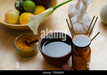 A countertop arrangement of ayurvedic turmeric spice, oil and massaging tools and an exotic flower used in Ayurveda massage. - Stock Image