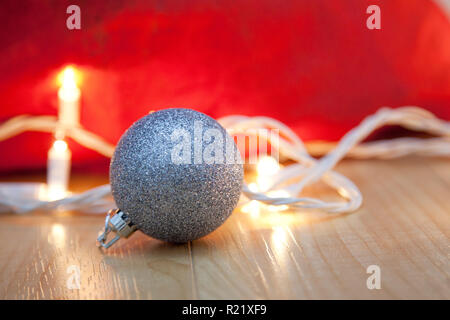 Red bag with white twinkling christmas lights and a silver ornament - Stock Image