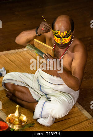 Vertical aerial view of a Kathakali performer applying his distinctive make up in Kerala, India. - Stock Image