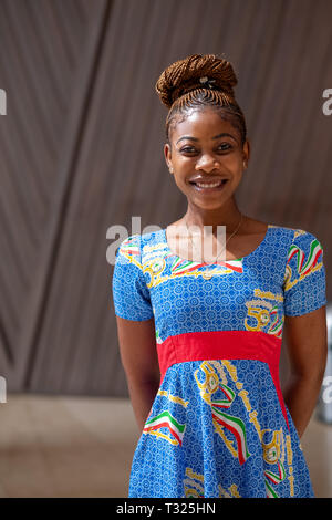 A smiling beautiful young woman wearing a dress made from the national colours of Equatorial Guinea - Stock Image