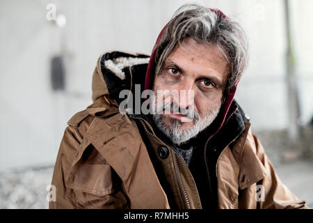 A close up portrait of homeless dirty beggar man sitting outdoors. - Stock Image