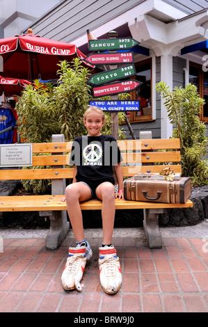 11 year old child sitting outside Bubba Gump restaurant in Kailua-Kona. Big Island, Hawaii - Stock Image