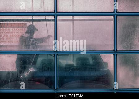 Man washing his car using a pressure washer at a self serve carwash - Stock Image