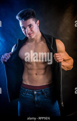 Young muscleman standing shirtless on black background - Stock Image