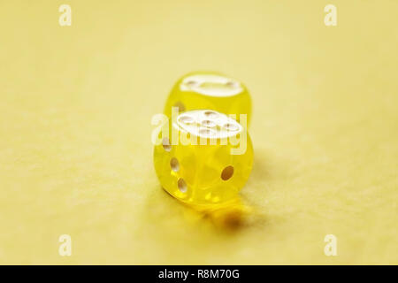 A vibrant monochromatic macro with depth of field about two yellow glass gambling dice with two numbers, two and five on a yellow background. - Stock Image