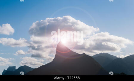 Dramatic view of Christ The Redeemer Statue on Corcovado Hill, Rio de Janeiro, Brazil - UNESCO World Heritage Site - dramatic sun-flare - Stock Image