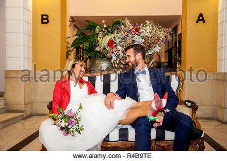 Couple of newlyweds sit on a hotel reception sofa. - Stock Image