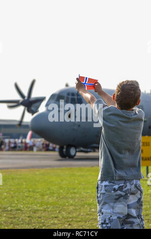Royal Norwegian Air Force Lockheed C-130J Hercules named Nanna being welcomed to North Weald, Essex, UK by boy holding Norwegian flag - Stock Image