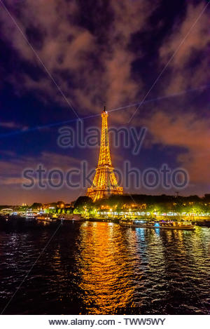 The illuminated Eiffel Tower with the River Seine in the foreground, Paris, France. - Stock Image