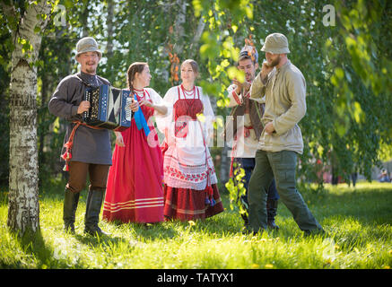 People in traditional Russian clothes are standing in the woods and talking - one of them plays the accordion and singing - gorizontal view - Stock Image