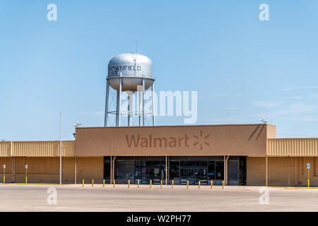Brownfield, USA - June 8, 2019: Texas countryside industrial town with old vintage run-down Walmart and water tank with sign - Stock Image