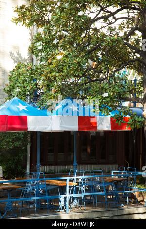 View of the café tables with Texas flag pattern on umbrellas, Riverwalk, San Antonio, Texas USA - Stock Image