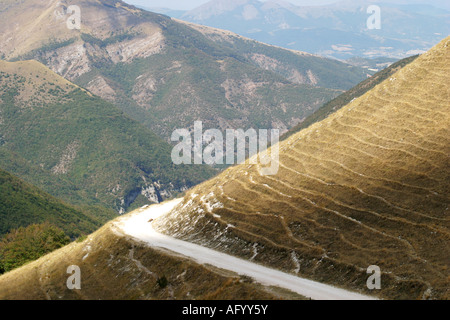 access road 'strada bianca' curves around the  Sasso Tetto  mountain at Pintura  in the Sibillini National - Stock Image