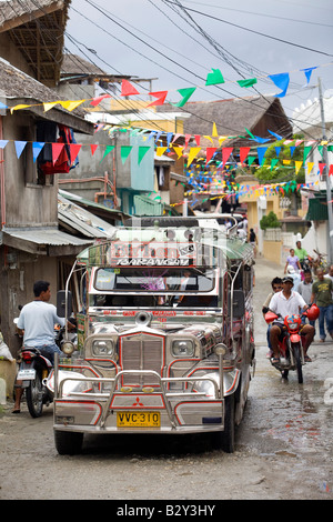 A Jeepney makes its way down a street in Sabang near Puerto Galera, Oriental Mindoro, Philippines. - Stock Image