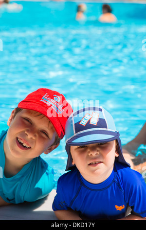 Two happy boys on holiday by the swimming pool. - Stock Image