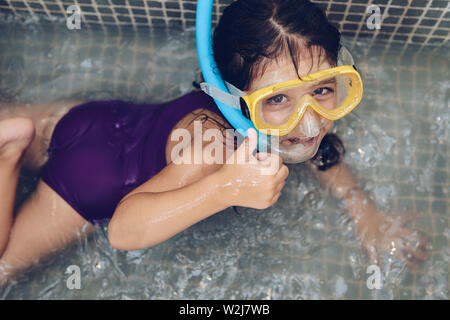 portrait of a beautiful little girl having fun swimming with snorkel goggles in the tub while taking a bath in the bathtub, kids hygiene concept - Stock Image