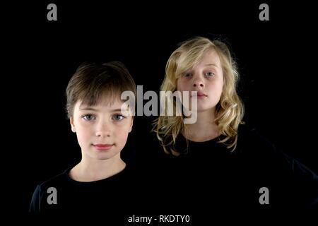 Portrait of two moody young girls against a black background - Stock Image