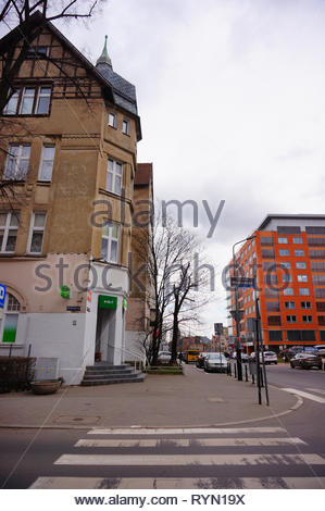 Poznan, Poland - March 8, 2019: Zebra crossing leading to a small Zabka grocery store in a old building on the Slowackiego street. - Stock Image