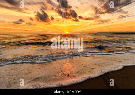 Ocean sunset is an ocean sunset with inspirational rays bursting forth from the ocean sunset. - Stock Image