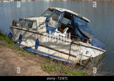 An abandoned cabin cruiser slowly sinks into the Thames opposite the University Boathouses on the Thames in Oxford - Stock Image